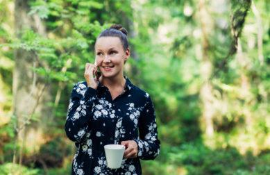 nainen puhuu puhelimeen metsässä kahvikuppi kädessä